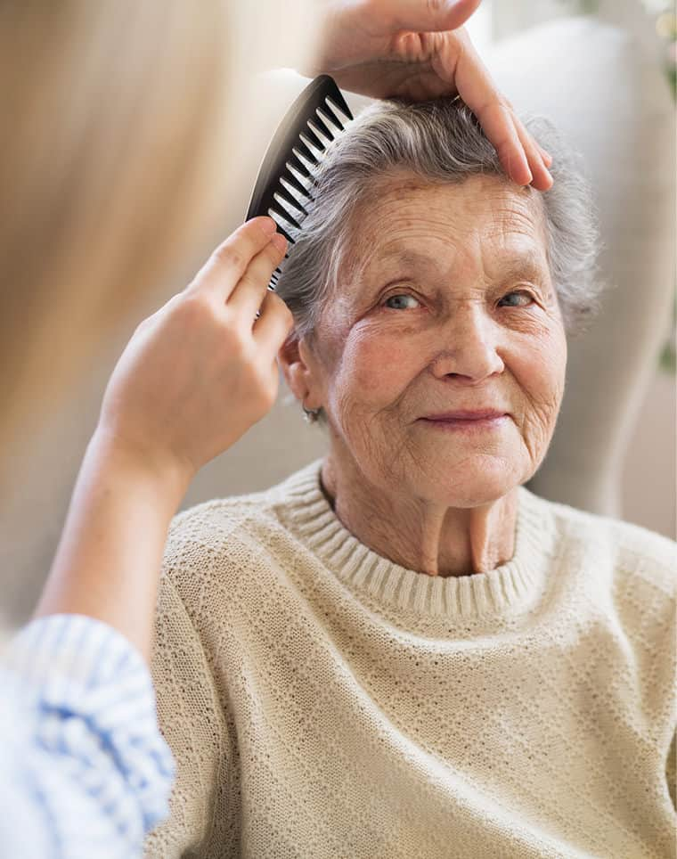 The extra mile: Wellbeing - a hairdresser combing lady's hair